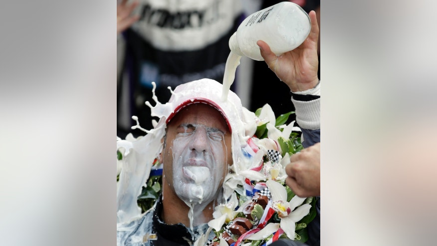 FOR USE AS DESIRED, YEAR END PHOTOS - FILE - Tony Kanaan, of Brazil, celebrates with winners milk after winning the Indianapolis 500 auto race at the Indianapolis Motor Speedway in Indianapolis, Sunday, May 26, 2013. (AP Photo/Michael Conroy, File)