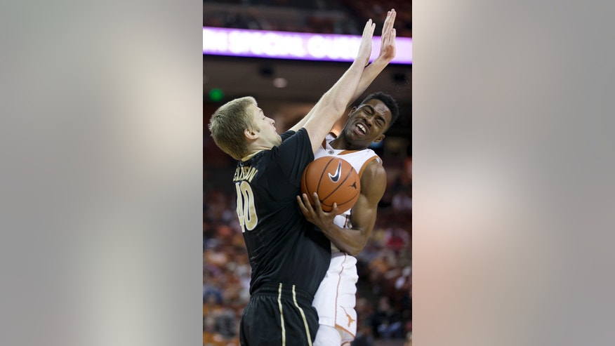 Texas's Isaiah Taylor, right, runs into the defense of Vanderbilt's Josh Henderson during the first half of an NCAA college basketball game on Monday, Dec. 2, 2013, in Austin Texas. (AP Photo/Austin American-Statesman, Deborah Cannon)