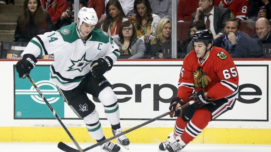 Dallas Stars left wing Jamie Benn (14) advances the puck into the Chicago Blackhawks' zone past center Andrew Shaw during the first period of an NHL hockey game Tuesday, Dec. 3, 2013, in Chicago. (AP Photo/Charles Rex Arbogast)