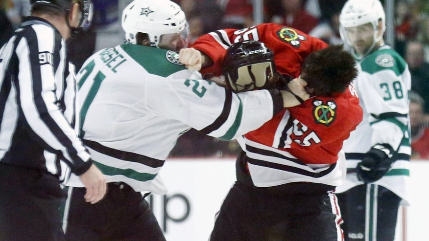 Dallas Stars left wing Antoine Roussel, left, and Chicago Blackhawks center Andrew Shaw fight during the first period of an NHL hockey game Tuesday, Dec. 3, 2013, in Chicago. (AP Photo/Charles Rex Arbogast)