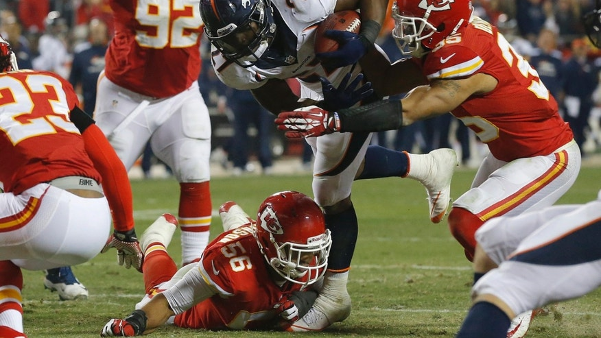 Denver Broncos running back Knowshon Moreno (27) gets stopped by Kansas City Chiefs inside linebacker Derrick Johnson (56) and defensive back Quintin Demps (35) during the second half of an NFL football game, Sunday, Dec. 1, 2013, in Kansas City, Mo. (AP Photo/Orlin Wagner)