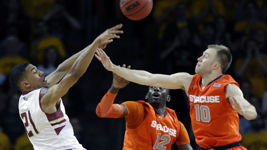 Boston College guard Olivier Hanlan (21) attempts to shoot over the defense of Syracuse center Baye-Moussa Keita (12), and guard Trevor Cooney (10) during the second half of an NCAA college basketball game in Boston, Monday, Jan. 13, 2014. Syracuse won 69-59. (AP Photo/Stephan Savoia)