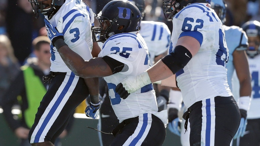 Duke's Jamison Crowder (3) celebrates his touchdown against North Carolina with teamamtes Jela Duncan (25) and Matt Skura (62) during the second half of an NCAA college football game in Chapel Hill, N.C., Saturday, Nov. 30, 2013. Duke won 27-25. (AP Photo/Gerry Broome)