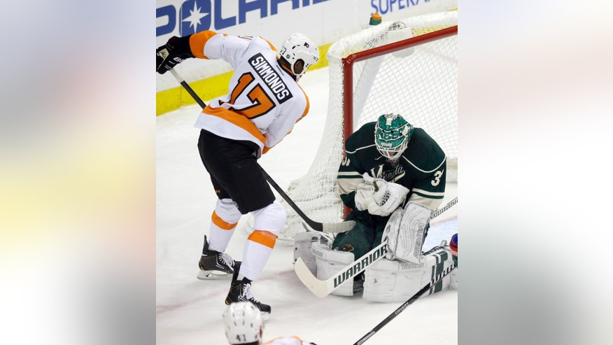 Minnesota Wild goalie Josh Harding, right, stops a shot by Philadelphia Flyers'  Wayne Simmonds in the first period of an NHL hockey game, Monday,  Dec. 2, 2013, in St. Paul, Minn. (AP Photo/Jim Mone)