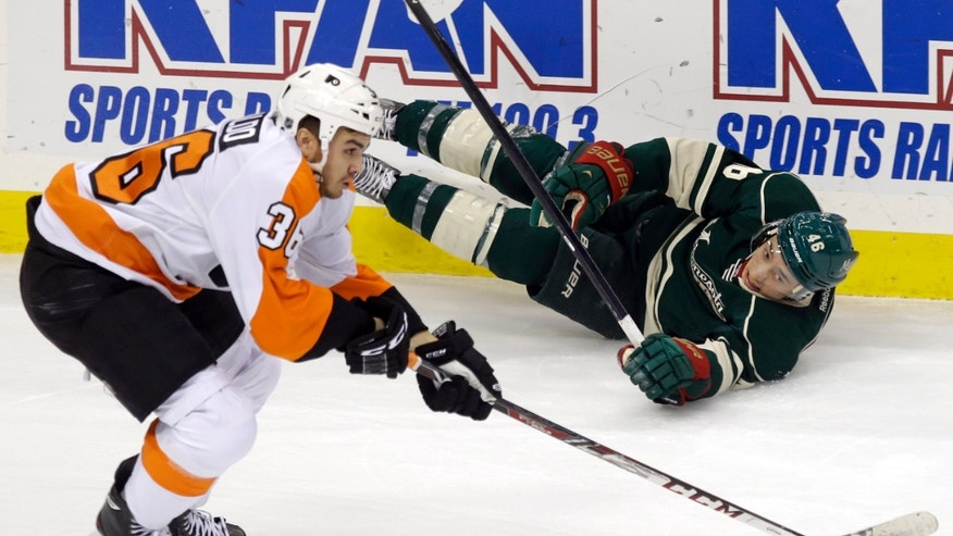 Minnesota Wild's Jared Spurgeon, right, can only watch Philadelphia Flyers center Zac Rinaldo skate away with the puck after he fell down in the first period of an NHL hockey game, Monday,  Dec. 2, 2013, in St. Paul, Minn. (AP Photo/Jim Mone)