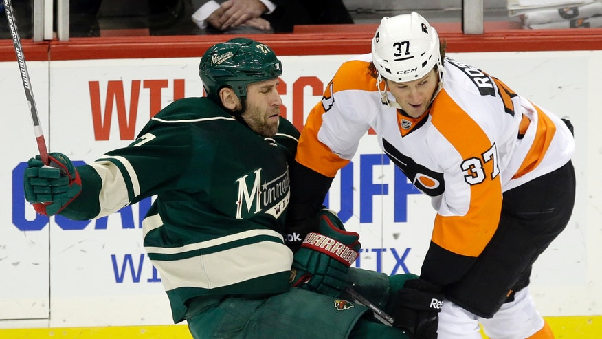 Minnesota Wild's Mike Rupp, left, gets sent to the ice by Philadelphia Flyers' Jay Rosehill in the first period of an NHL hockey game, Monday,  Dec. 2, 2013, in St. Paul, Minn. (AP Photo/Jim Mone)