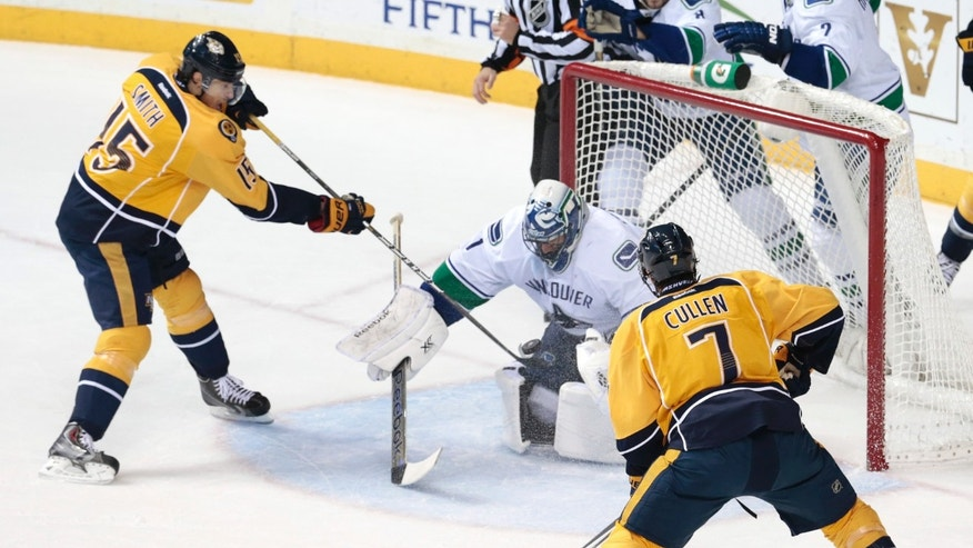 Vancouver Canucks goalie Roberto Luongo (1) blocks the puck as Nashville Predators forward Craig Smith (15) and Matt Cullen (7) try for the rebound in the first period of an NHL hockey game Tuesday, Dec. 3, 2013, in Nashville, Tenn. (AP Photo/Mark Humphrey)