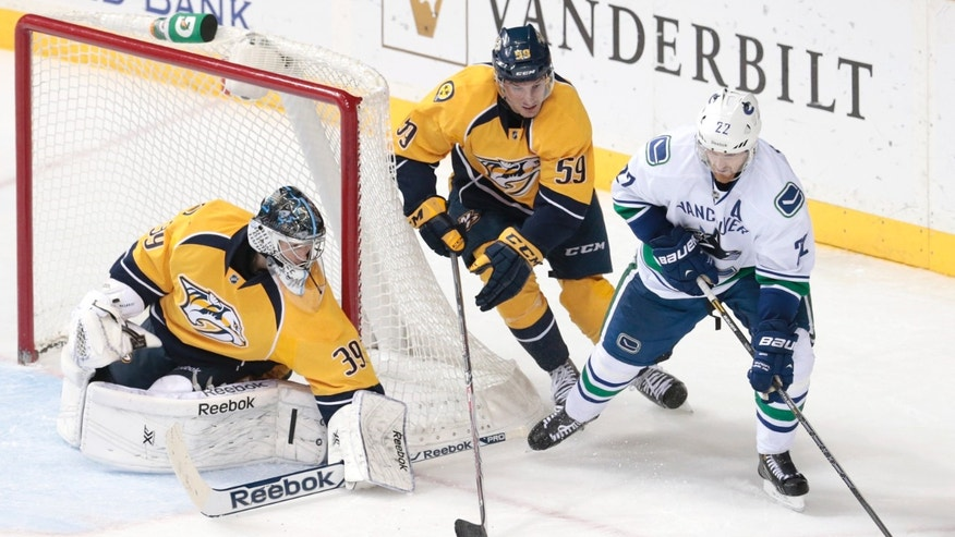 Vancouver Canucks left wing Daniel Sedin (22), of Sweden, circles the net as Nashville Predators goalie Marek Mazanec (39), of the Czech Republic,  and Roman Josi (59), of Switzerland, defend in the second period of an NHL hockey game Tuesday, Dec. 3, 2013, in Nashville, Tenn. (AP Photo/Mark Humphrey)