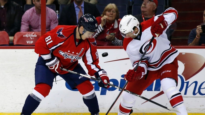 Washington Capitals defenseman Dmitry Orlov (81), from Russia, and Carolina Hurricanes right wing Radek Dvorak (18), from the Czech Republic, keep their eye on the puck as it bounces up, in the first period of an NHL hockey game, Tuesday, Dec. 3, 2013, in Washington. (AP Photo/Alex Brandon)