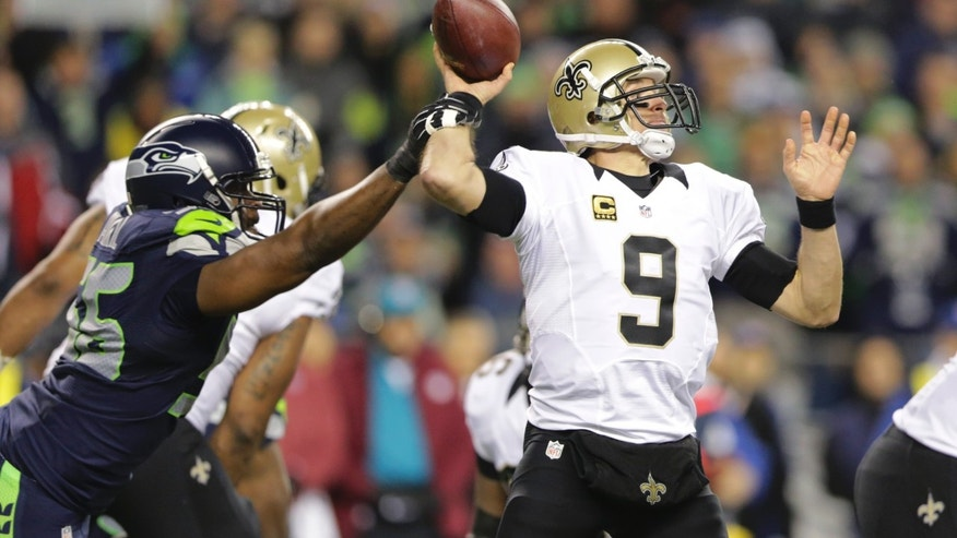 Seattle Seahawks defensive end Cliff Avril, left, causes New Orleans Saints quarterback Drew Brees (9) to fumble in the first half of an NFL football game, Monday, Dec. 2, 2013, in Seattle. Seahawks defensive end Michael Bennett recovered the fumble and ran for a touchdown. (AP Photo/Scott Eklund)