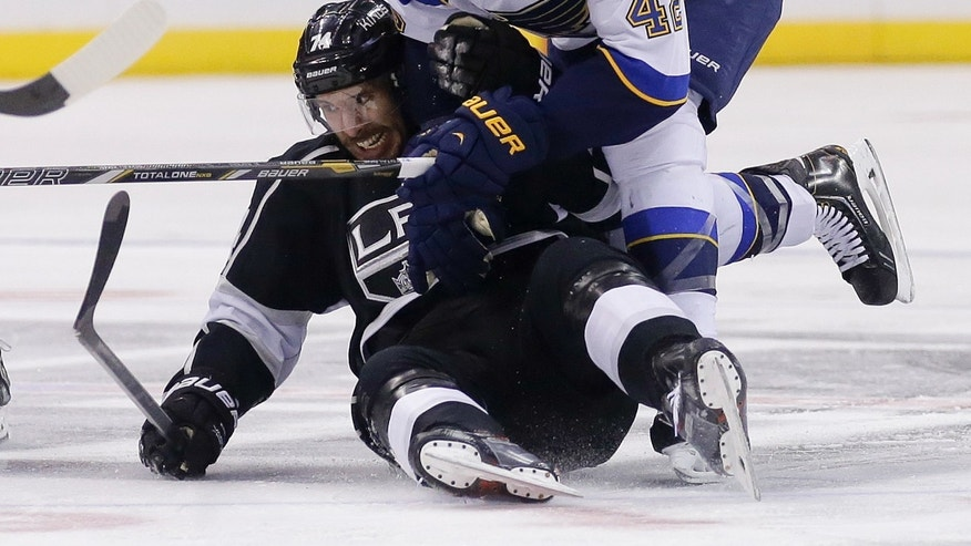 St. Louis Blues center David Backes, top, trips Los Angeles Kings left wing Dwight King during the second period of an NHL hockey game in Los Angeles, Monday, Dec. 2, 2013. (AP Photo/Chris Carlson)