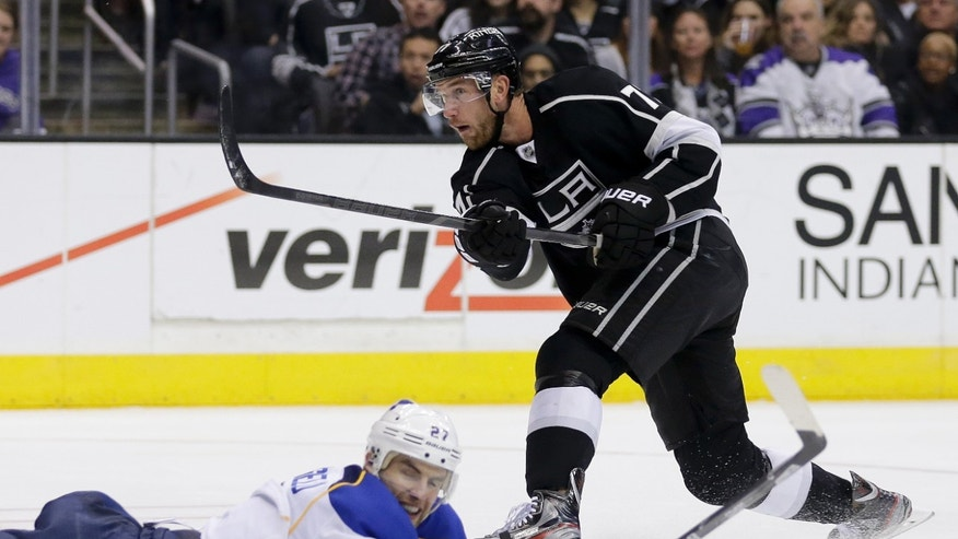 Los Angeles Kings center Jeff Carter, right, shoots over the top of St. Louis Blues defenseman Alex Pietrangelo during the second period of an NHL hockey game in Los Angeles, Monday, Dec. 2, 2013. (AP Photo/Chris Carlson)