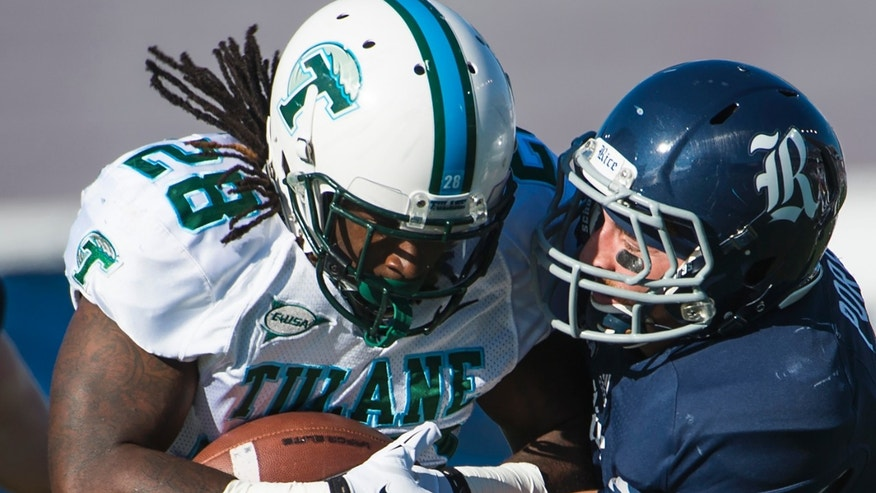 Tulane running back Rob Kelley (28) is stopped for a loss by Rice safety Paul Porras (24)  during the first quarter of an NCAA college football game at Rice Stadium, Saturday, Nov. 30, 2013, in Houston. (AP Photo/Houston Chronicle, Smiley N. Pool) MANDATORY CREDIT