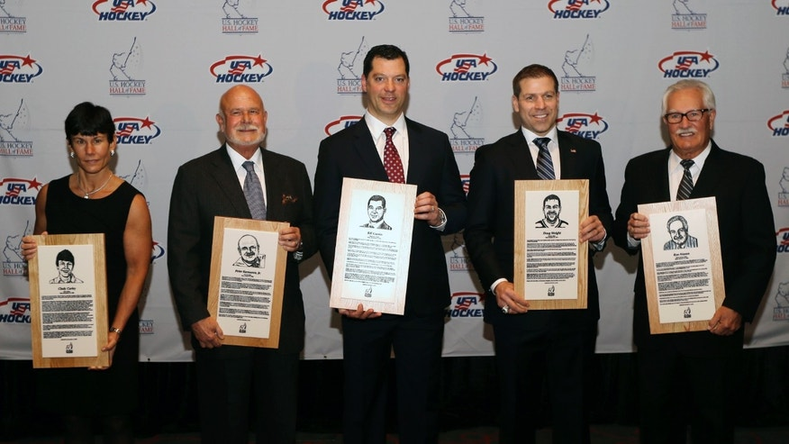 From left, Cindy Curley, Peter Karmanos Jr., Bill Guerin, Doug Weight, and Ron Mason stand with their plaques before being inducted into the United States Hockey Hall of Fame in Detroit, Monday, Dec. 2, 2013. (AP Photo/Carlos Osorio)