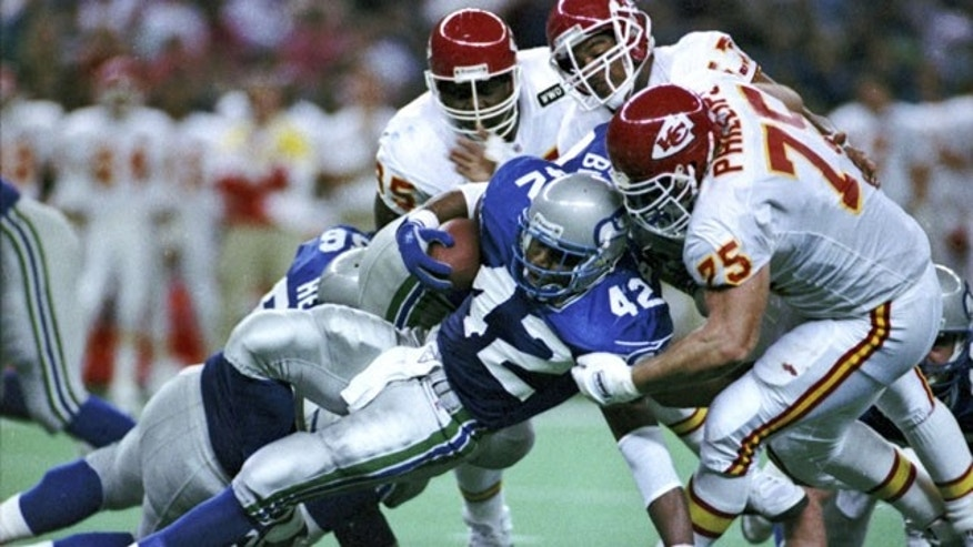 FILE - In this Nov. 22, 1992, file photo, Kansas City Chiefs' Tom Sims, rear left, Chris Martin, rear right, and Joe Phillips, right, tackle Seattle Seahawks running back Chris Warren during an NFL football game in Seattle. (AP)