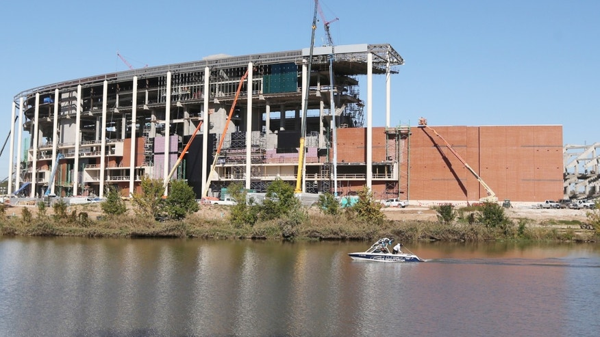 FILE - In this Nov. 13, 2013 photo, a boat floats past the new Baylor football stadium under construction along the banks of the Brazos River in Waco, Texas. Baylor plays its final game at Floyd Casey Stadium Saturday, Dec. 7, 2013, after 64 seasons. (AP Photo/Waco Tribune Herald, Rod Aydelotte, File)