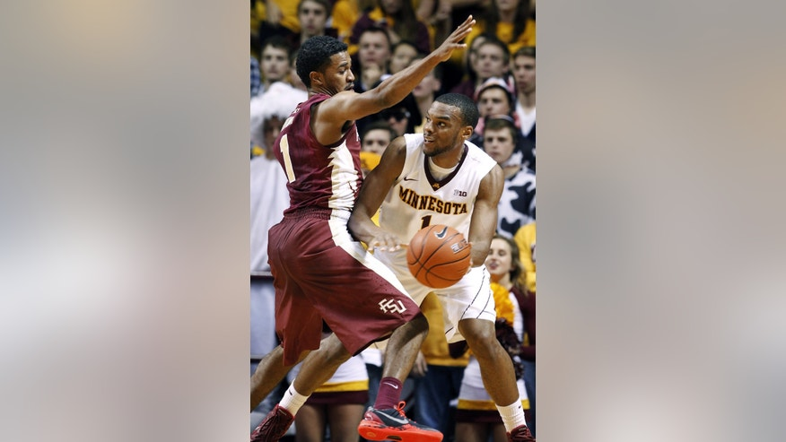 Minnesota guard Andre Hollins, right, looks to pass under pressure from Florida State guard Devon Bookert, left, during the first half of an NCAA college basketball game in Minneapolis, Tuesday, Dec. 3, 2013. (AP Photo/Ann Heisenfelt)