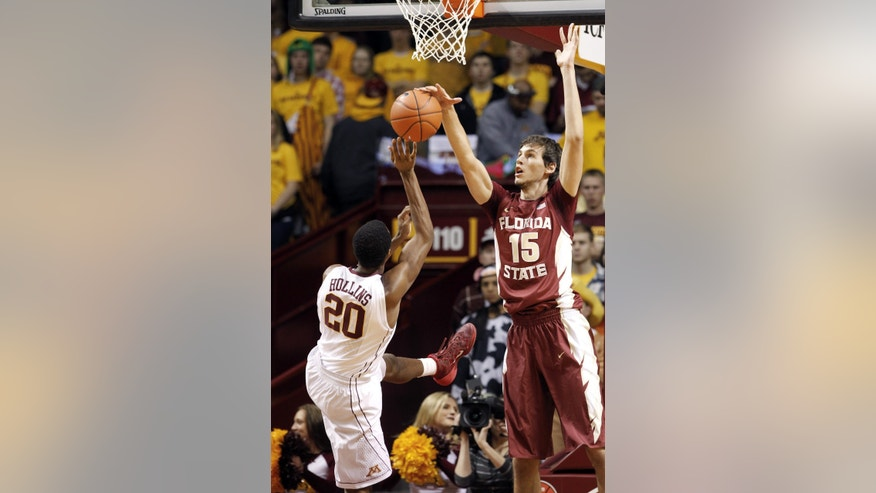 Florida center Boris Bojanovsky (15) deflects shot attempt by Minnesota guard Austin Hollins (20) during the first half of an NCAA college basketball game in Minneapolis, Tuesday, Dec. 3, 2013. (AP Photo/Ann Heisenfelt)