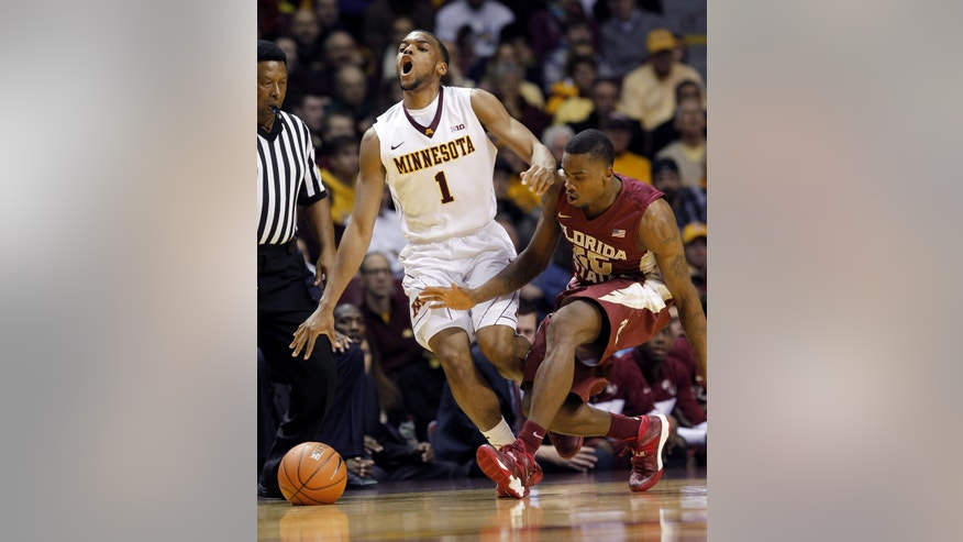 Minnesota guard Andre Hollins (1) loses control of the ball as he is fouled by Florida State guard Aaron Thomas, right, during the first half of an NCAA college basketball game in Minneapolis, Tuesday, Dec. 3, 2013. (AP Photo/Ann Heisenfelt)