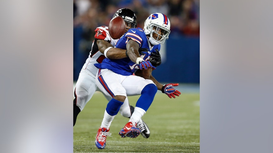 Buffalo Bills wide receiver Stevie Johnson (13) fumbles as he is tackled by Atlanta Falcons cornerback Robert McClain (27) during the second half of an NFL football game on Sunday, Dec. 1, 2013, in Toronto. (AP Photo/Gary Wiepert)