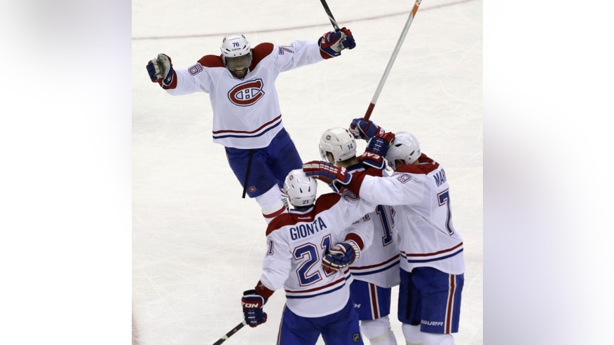 Montreal Canadiens' P.K. Subban (76), Brian Gionta (21), Tomas Plekanec (14), of the Czech Republic, and Andrei Markov (79), of Russia, celebrate a goal by teammate David Desharnais to tie the score 3-3 with 36 seconds to play during the third period of an NHL hockey game against the New Jersey Devils, Wednesday, Dec. 4, 2013, in Newark, N.J. (AP Photo/Julio Cortez)