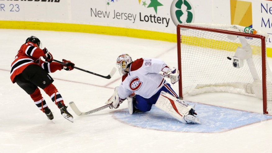 New Jersey Devils left wing Reid Boucher, left, scores a shootout goal during his NHL debut on a shot against Montreal Canadiens goalie Peter Budaj, of Slovakia, during an NHL hockey game, Wednesday, Dec. 4, 2013, in Newark, N.J. The Canadiens won 4-3. (AP Photo/Julio Cortez)