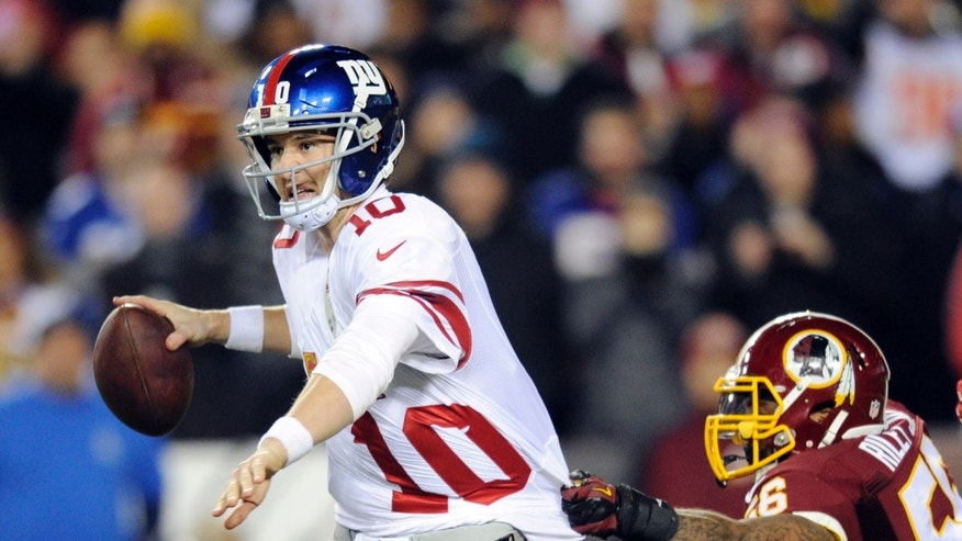New York Giants quarterback Eli Manning (10) looks to pass as Washington Redskins inside linebacker Perry Riley hangs onto his jersey during the second half of an NFL football game Sunday, Dec. 1, 2013, in Landover, Md. (AP Photo/Nick Wass)