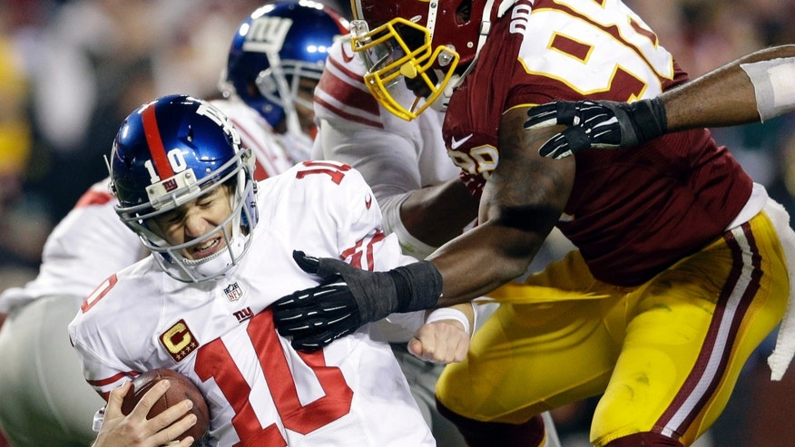New York Giants quarterback Eli Manning (10) is sacked by Washington Redskins outside linebacker Brian Orakpo (98) during the second half of an NFL football game Sunday, Dec. 1, 2013, in Landover, Md. (AP Photo/Patrick Semansky)
