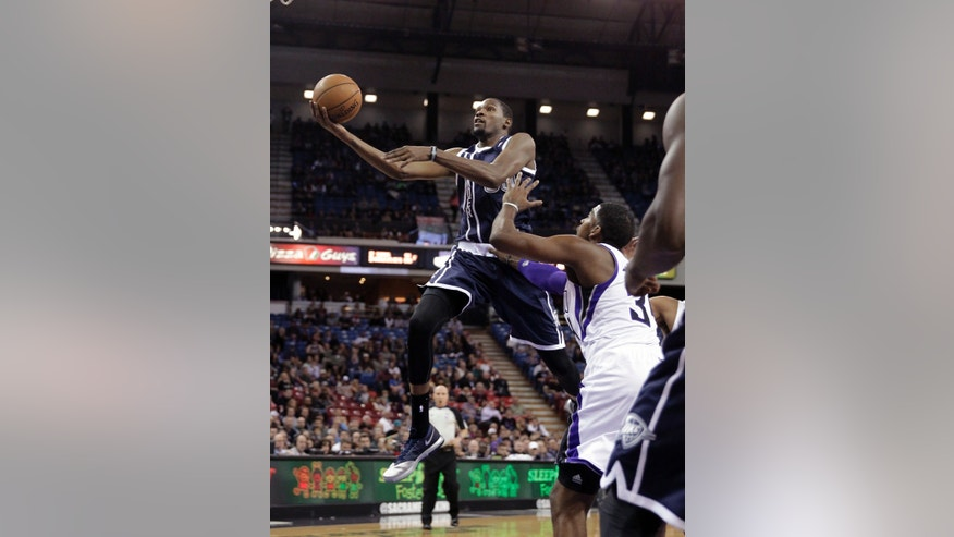 Oklahoma City Thunder forward Kevin Durant, left, drives to the basket against Sacramento Kings' Jason Thompson during the first quarter of an NBA basketball game in Sacramento, Calif., Tuesday, Dec. 3, 2013. (AP Photo/Rich Pedroncelli)