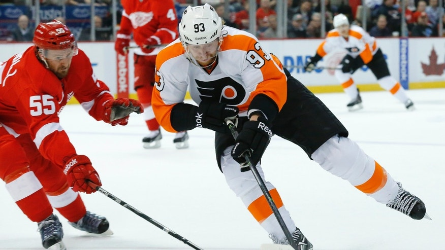 Philadelphia Flyers right wing Jakub Voracek (93), of the Czech Republic, and Detroit Red Wings defenseman Niklas Kronwall (55), of Sweden, battle for the puck in the first period of an NHL hockey game in Detroit, Wednesday, Dec. 4, 2013. (AP Photo/Paul Sancya)