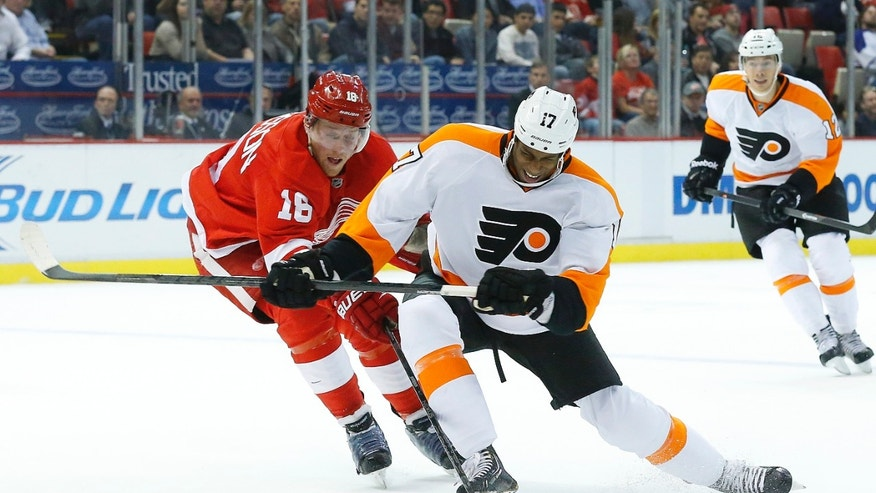 Philadelphia Flyers right wing Wayne Simmonds (17) and Detroit Red Wings center Joakim Andersson (18), of Sweden, battle for position in the first period of an NHL hockey game in Detroit, Wednesday, Dec. 4, 2013. (AP Photo/Paul Sancya)