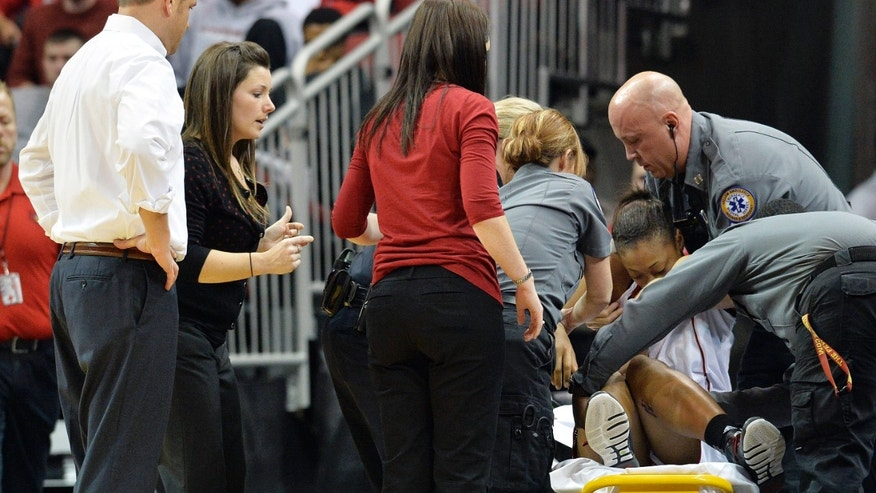 Louisville's Antonita Slaughter is placed on a stretcher by medical personnel following her collapse during the first half of an NCAA college basketball game against Missouri State, Tuesday, Dec. 3, 2013, in Louisville, Ky. (AP Photo/Timothy D. Easley)