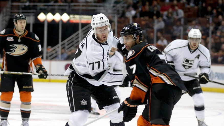Los Angeles Kings center Jeff Carter, left, shoots past Anaheim Ducks center Andrew Cogliano during the first period of an NHL hockey game in Anaheim, Calif., Tuesday, Dec. 3, 2013. (AP Photo/Chris Carlson)