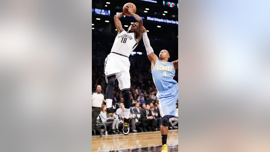 Denver Nuggets guard Randy Foye (4) fouls Brooklyn Nets guard Tyshawn Taylor (10) in the first half of an NBA basketball game Tuesday, Dec. 3, 2013, in New York. (AP Photo/Kathy Willens)