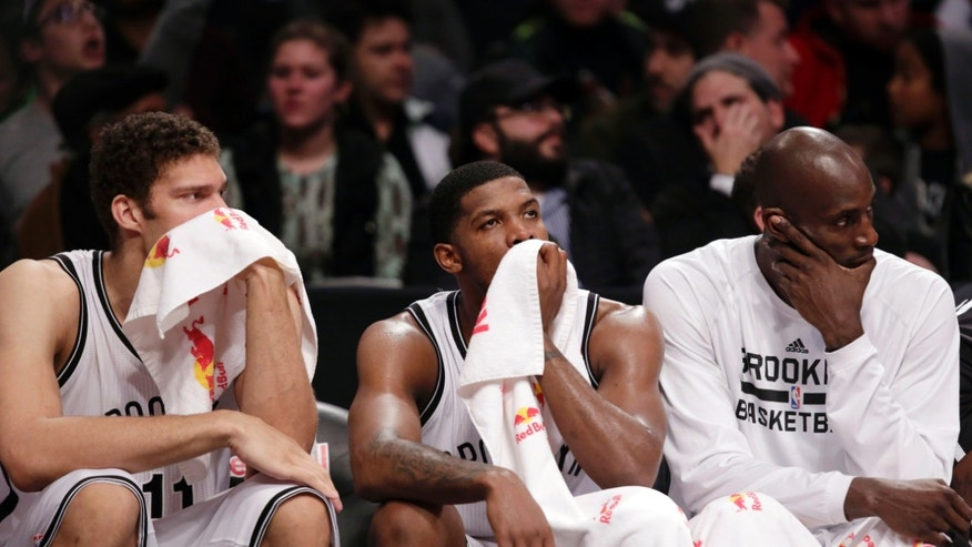 Brooklyn Nets forward Brook Lopez, left, guard Joe Johnson, center, and forward Kevin Garnett sit on the bench during  the second half of an NBA basketball game against the Denver Nuggets, Tuesday, Dec. 3, 2013, in New York. The Nuggets won 111-87. (AP Photo/Kathy Willens)