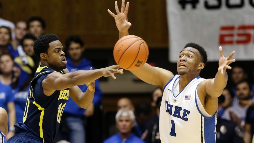 Duke's Jabari Parker (1) guards Michigan's Derrick Walton Jr. during the first half of an NCAA college basketball game in Durham, N.C., Tuesday, Dec. 3, 2013. (AP Photo/Gerry Broome)
