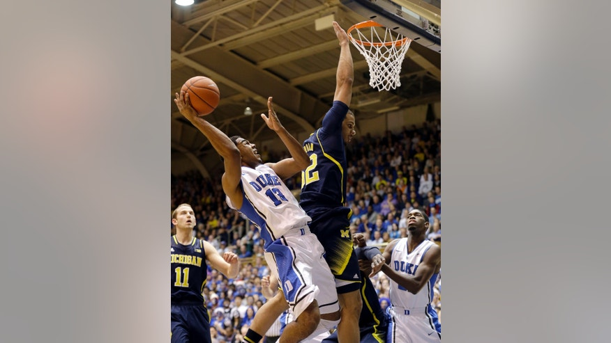 Duke's Matt Jones (13) drives to the basket as Michigan's Jordan Morgan defends during the first half of an NCAA college basketball game in Durham, N.C., Tuesday, Dec. 3, 2013. (AP Photo/Gerry Broome)