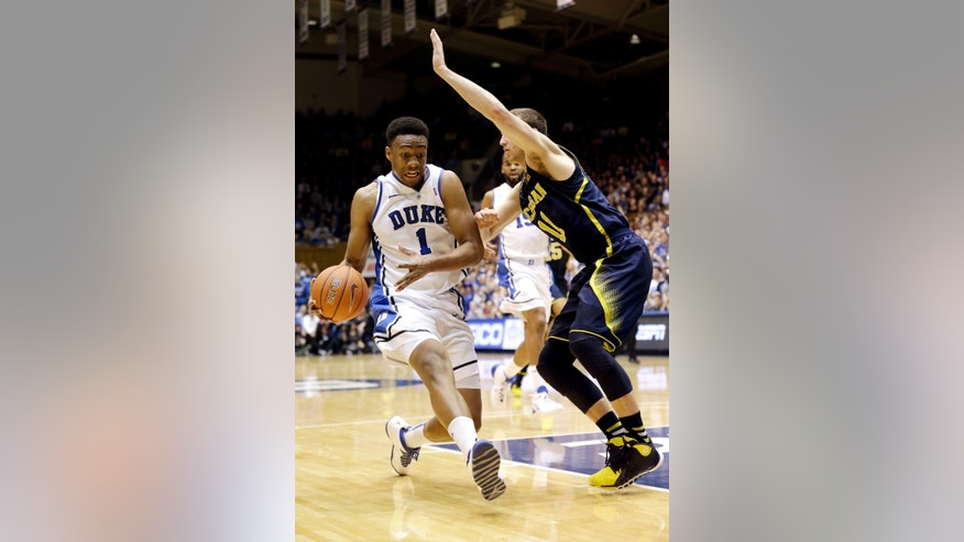 Duke's Jabari Parker (1) is guarded by Michigan's Nik Stauskas (11) during the first half of an NCAA college basketball game in Durham, N.C., Tuesday, Dec. 3, 2013. (AP Photo/Gerry Broome)