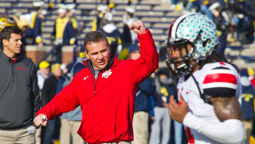 FILE - In this Nov. 30, 2013 file photo,  Ohio State head coach Urban Meyer responds to cheers from fans in Michigan Stadium as his team takes the field before an NCAA college football game against Michigan in Ann Arbor, Mich.  It seems as if No. 2 Ohio State has spent the past three months in a pressure-cooker. Now, after squeaking out its biggest win of the season against its bitter rival, the Buckeyes have to turn around and play yet another major showdown. They meet No. 10 Michigan State in the Big Ten championship game on Saturday. (AP Photo/Tony Ding, File)