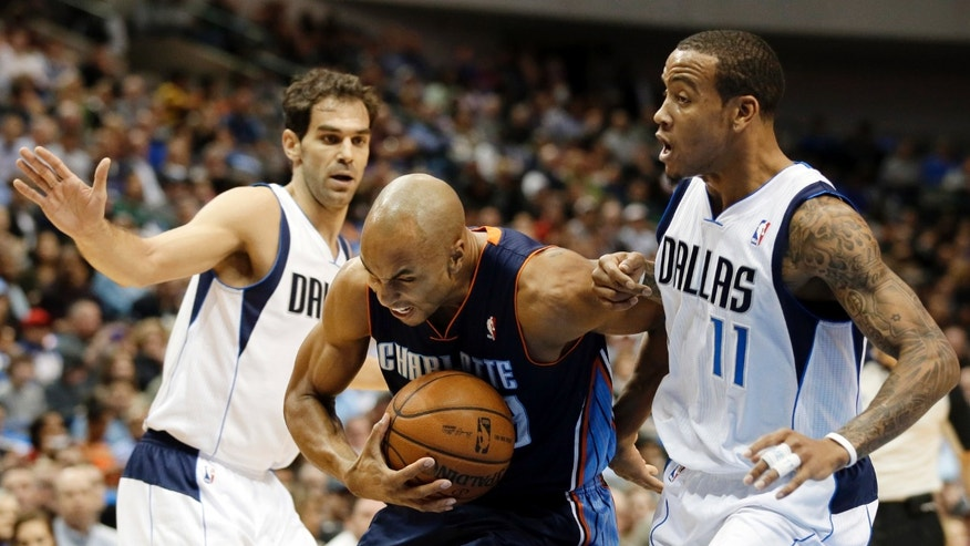 Charlotte Bobcats' Gerald Henderson, center, is fouled going to the basket  by Dallas Mavericks' Monta Ellis (11) as Jose Calderon, left, of Spain, stands by in the first half of an NBA basketball game Tuesday, Dec. 3, 2013, in Dallas. (AP Photo/Tony Gutierrez)
