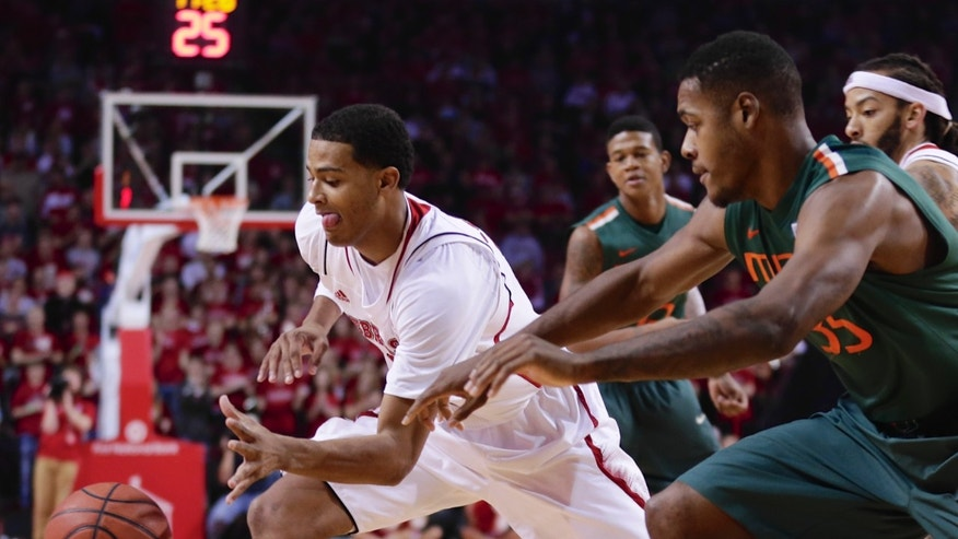 Nebraska's Shavon Shields, left, steals a ball from Miami's James Kelly (35), in the first half of an NCAA college basketball game  in Lincoln, Neb., Wednesday, Dec. 4, 2013. (AP Photo/Nati Harnik)