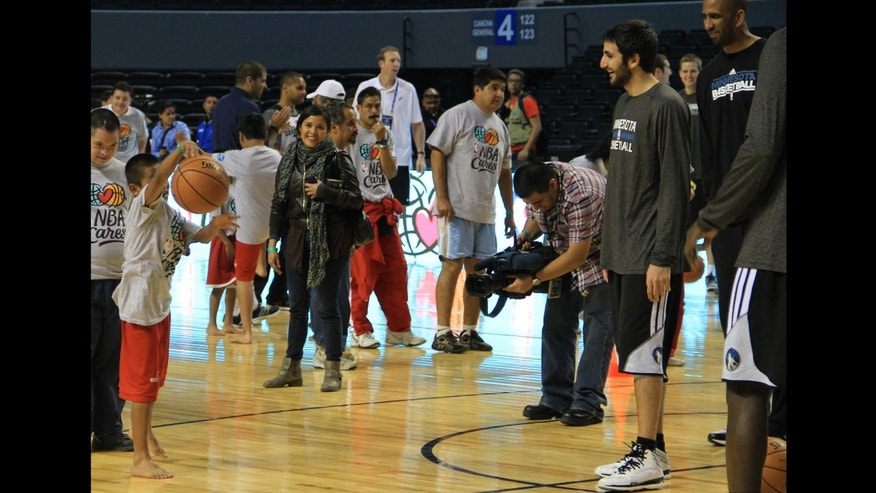 The Minnesota Timberwolves' Spanish point guard, Ricky Rubio, works with one member of Oaxaca's Trique barefoot boys basketball team, Dec. 3, 2013. (Photo: Nathaniel Parish Flannery.)