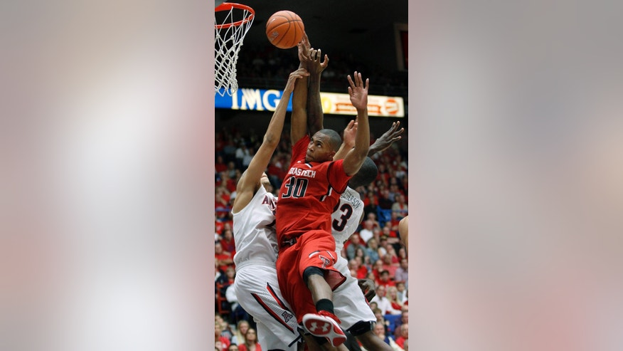 Texas Tech's Jaye Crockett (30) attempts to shoot for two as Arizona's Brandon Ashley, left, and Rondae Hollis-Jeffeerson (23) defend in the second half of an NCAA college basketball game on Tuesday, Dec. 3, 2013, in Tucson, Ariz. (AP Photo/John MIller)