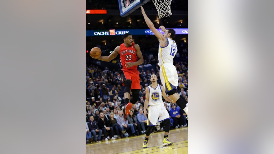 Toronto Raptors' Rudy Gay (22) looks to pass under the basket as Golden State Warriors' Andrew Bogut (12) defends during the first half of an NBA basketball game on Tuesday, Dec. 3, 2013, in Oakland, Calif. (AP Photo/Marcio Jose Sanchez)