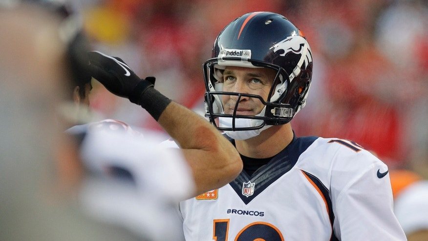 Denver Broncos quarterback Peyton Manning (18) looks at the scoreboard after throwing an interception during the first half of an NFL football game against the Kansas City Chiefs, Sunday, Dec. 1, 2013, in Kansas City, Mo. (AP Photo/Ed Zurga)