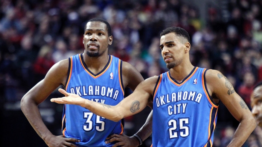 Oklahoma City Thunder's Kevin Durant, left, and Thabo Sefolosha, from Switzerland, talk during the first half of an NBA basketball game against the Portland Trail Blazers in Portland, Ore., Wednesday, Dec. 4, 2013. (AP Photo/Don Ryan)