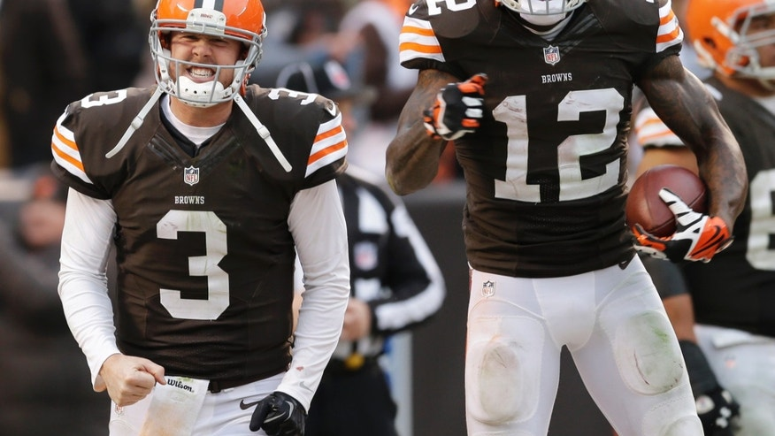 Cleveland Browns quarterback Brandon Weeden (3) celebrates with wide receiver Josh Gordon (12) after they connected on a 95-yard touchdown pass in the fourth quarter of an NFL football game against the Jacksonville Jaguars, Sunday, Dec. 1, 2013, in Cleveland. (AP Photo/Tony Dejak)