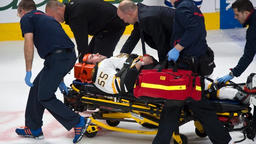 Boston Bruins' Johnny Boychuk is carried off the ice after taking a hit from Montreal Canadiens' Max Pacioretty during first period NHL hockey action Thursday, Dec. 5, 2013 in Montreal. (AP Photo/The Canadian Press, Paul Chiasson)