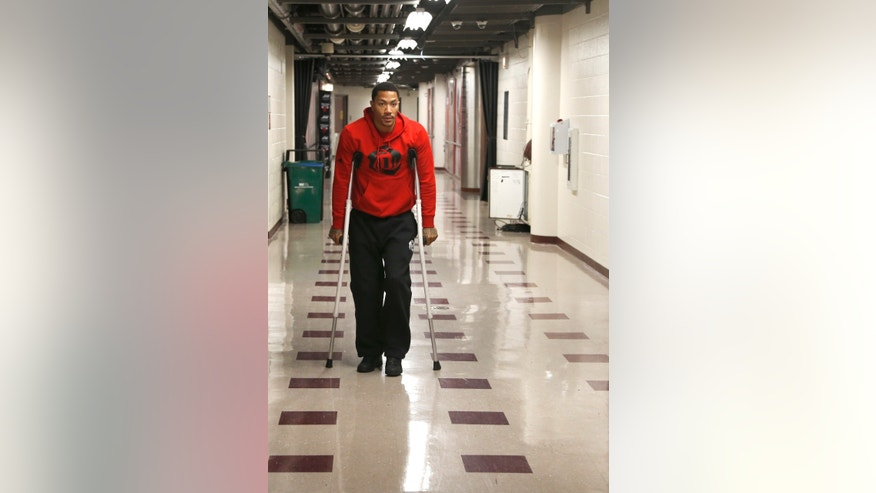 Chicago Bulls NBA basketball player  Derrick Rose walks down the hall on crutches to a news conference about his injured knee at the United Center Thursday, Dec. 5, 2013, in Chicago. (AP Photo/Charles Rex Arbogast)