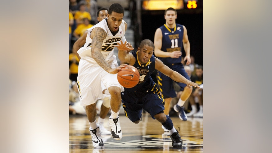 West Virginia's Gary Browne, center, tries to steal the ball from Missouri's Jabari Brown, left, as Nathan Adrian, right, looks on during the first half of an NCAA college basketball game Thursday, Dec. 5, 2013, in Columbia, Mo. (AP Photo/L.G. Patterson)